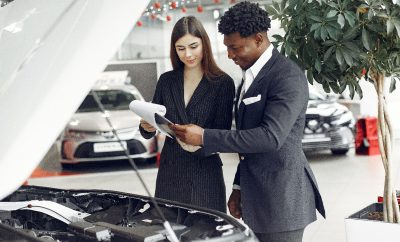 Two people looking at a piece of paper Description automatically generated with medium confidence